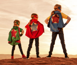 Three girls dressed at superheroes