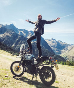Sam Pelly balanced on Royal Enfield motorbike